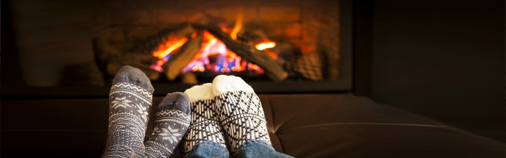 Two pairs of feet wearing warm winter socks warming in front of a fireplace